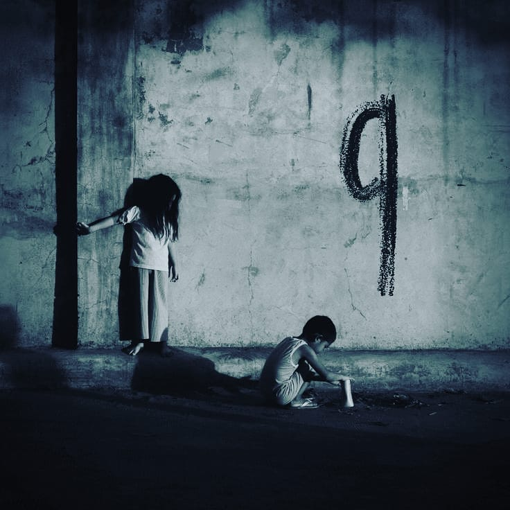 girl and boy in black and white photo on the street with number nine on the wall