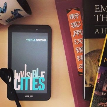 Invisible Cities by Italo Calvino Vintage Classics ebook in tablet with Asian books and Spanish cup on desk